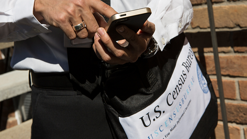 Man using phone, carrying US Census bag.