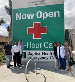 Group standing in front of big sign in front of Baptist Health Emergency Center