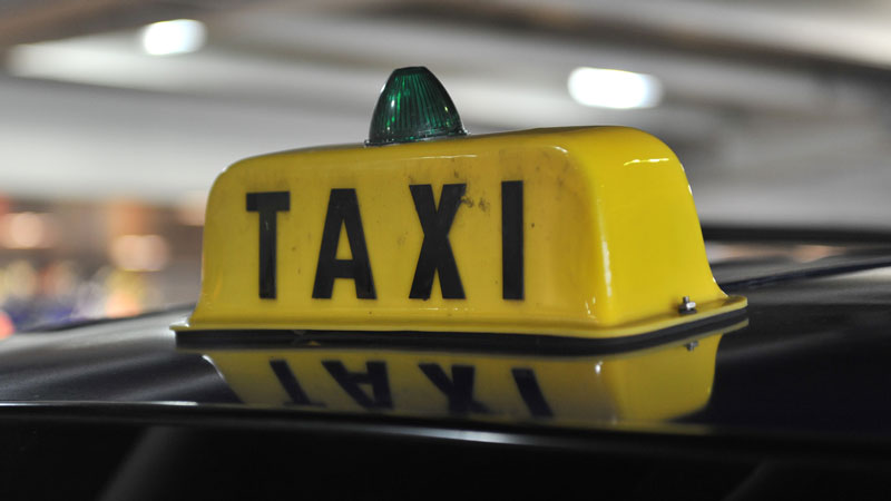 a taxi sign atop a vehicle