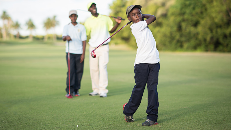 Boy swinging a golf club with father and brother watching behind him